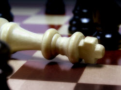 photo of a chessboard, showing a king on its side after checkmate