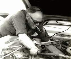 Guy working under the hood of a car